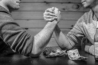 Arm wrestling over money
